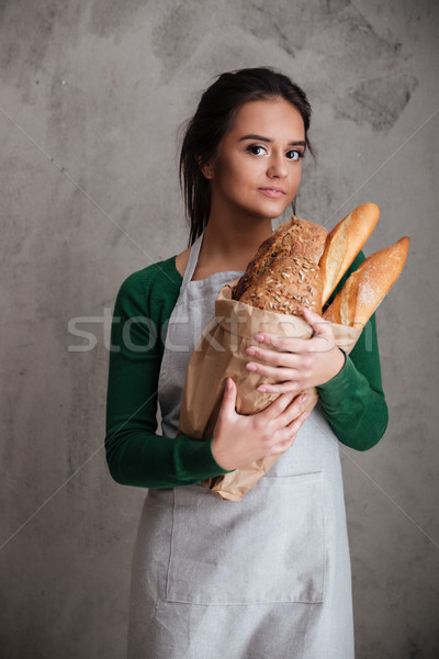 Young cheerful lady baker standing and holding bread. Stock photo © deandrobot
