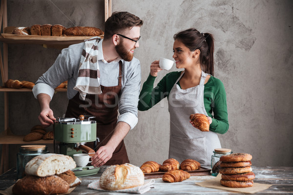 Cheerful loving couple bakers drinking coffee. Looking aside. Stock photo © deandrobot