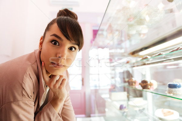 Woman standing at the glass showcase with patries inside cafe Stock photo © deandrobot