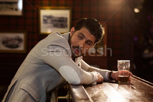 Jovem bêbado homem sessão contrariar pub Foto stock © deandrobot