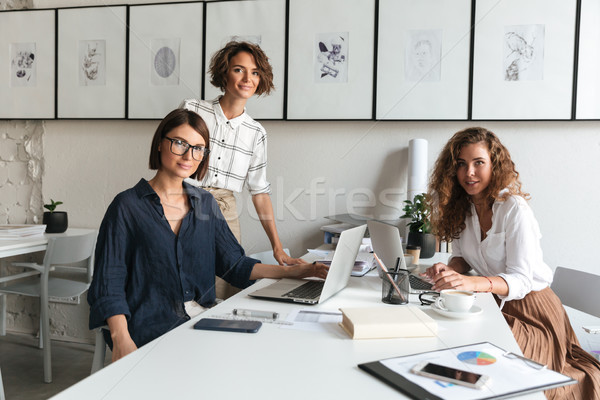 Side view of three women are discussing something Stock photo © deandrobot