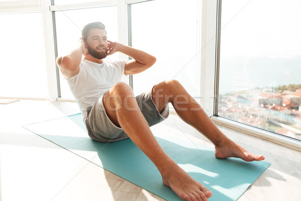 Smiling bearded man doing abdominals exercises near the window Stock photo © deandrobot