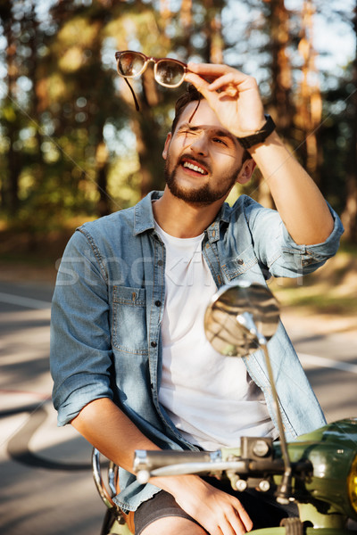 Handsome young bearded man sitting on scooter holding sunglasses Stock photo © deandrobot