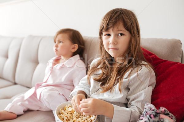 Portré kislány pattogatott kukorica ül kanapé kezek Stock fotó © deandrobot