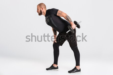 Portrait of a handsome sportsman doing stretching exercises before jogging Stock photo © deandrobot