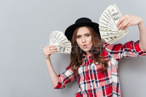 Portrait of a excited girl holding money banknotes Stock photo © deandrobot