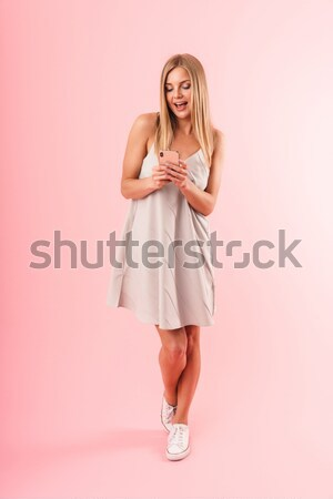 Full length portrait of an attractive woman in dress thinking Stock photo © deandrobot