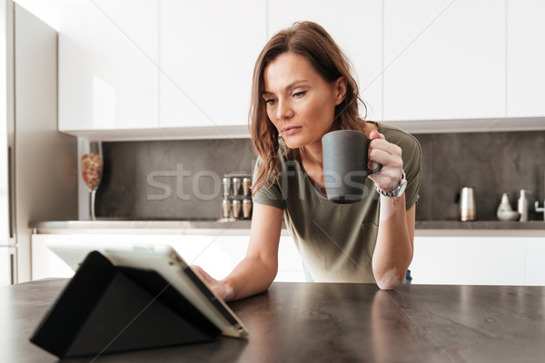Casual woman drinking coffee and using tablet computer Stock photo © deandrobot