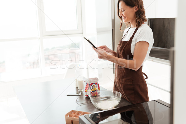 Side view of smiling casual woman using tablet computer Stock photo © deandrobot