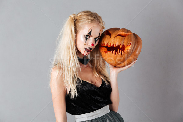 Mystery blonde woman in halloween make-up posing with carved pumpkin Stock photo © deandrobot