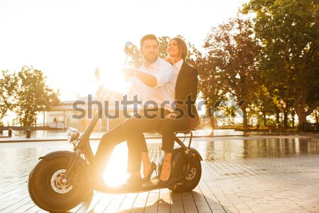 Full length image of attractive african couple rides on motorbike Stock photo © deandrobot