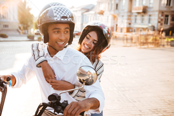 Image of Carefree african couple rides on modern motorbike Stock photo © deandrobot