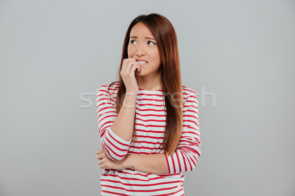 Portrait of a nervous asian girl biting her nails Stock photo © deandrobot