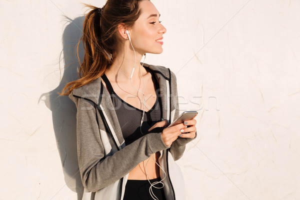 Close-up photo of cheerful brunette sport woman holding smartpho Stock photo © deandrobot