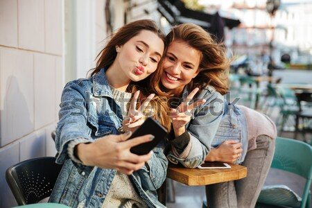 Two charming woman friends looking at mobile phone while sitting Stock photo © deandrobot