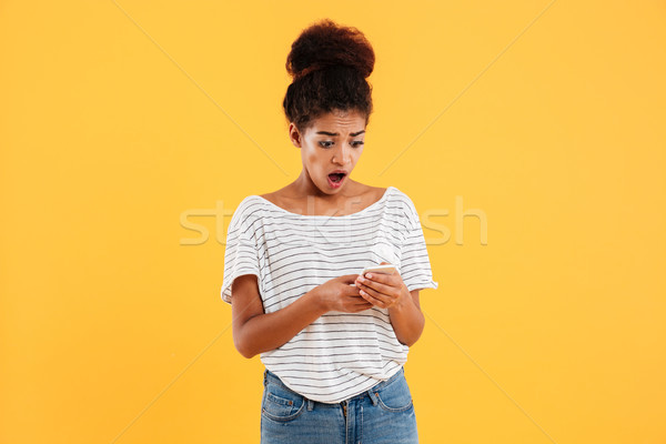 Shocked african lady using and typing smartphone isolated Stock photo © deandrobot
