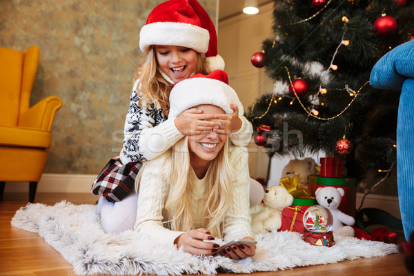 Playful little girl in Santa's hat covering her mothers eyes in  Stock photo © deandrobot