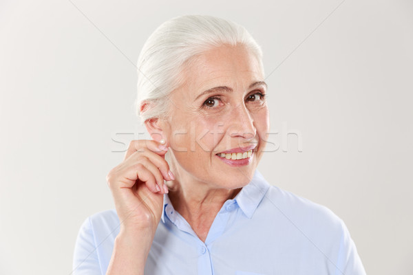 Portrait of smiling elderly woman touching her ear, looking at c Stock photo © deandrobot