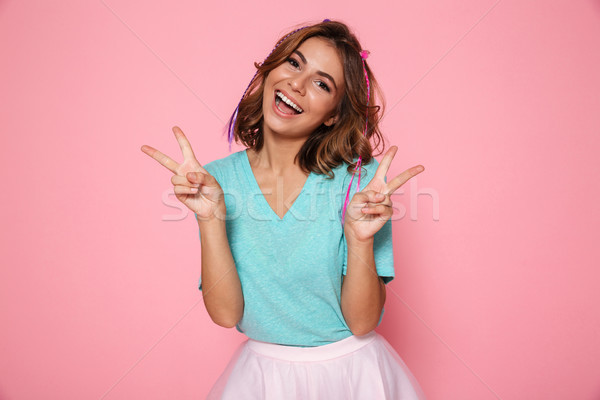 Stock photo: Happy cute brunette girl showing peace gesture with two hands, l