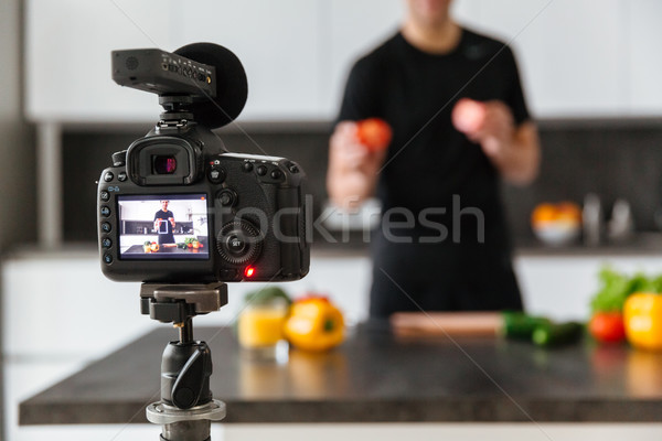 Close up of a video camera filming young man Stock photo © deandrobot