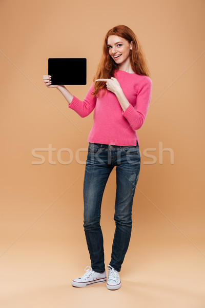 Full length portrait of a satisfied pretty redhead girl Stock photo © deandrobot