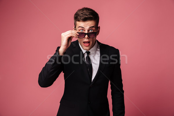 Shocked man taking off glasses and looking camera Stock photo © deandrobot