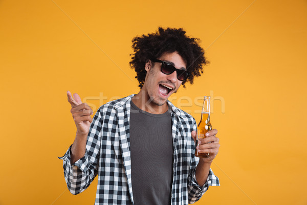 Portrait of a cheery happy african man in sunglasses Stock photo © deandrobot