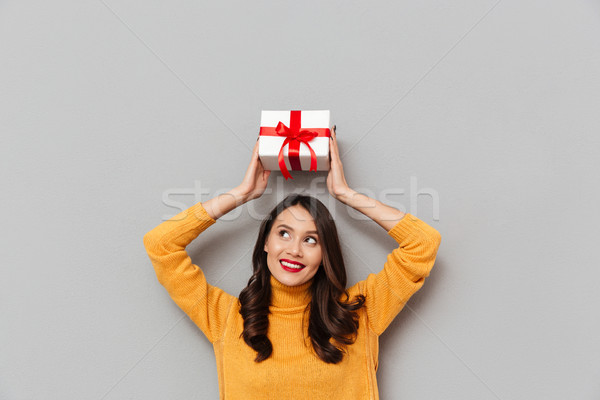 Smiling brunette woman in sweater holding gift box overhead Stock photo © deandrobot