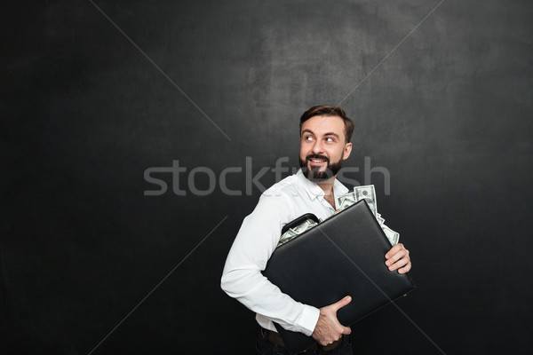 Portrait of happy rich businessman carrying briefcase full of do Stock photo © deandrobot