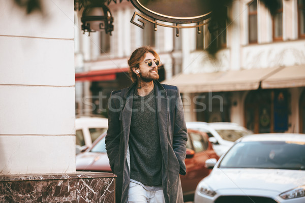 Portrait of a young bearded in earphones man Stock photo © deandrobot