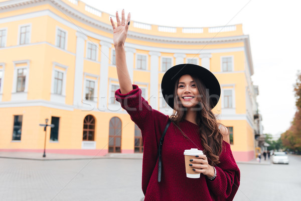 Happy brunette woman in hat and sweater waving away Stock photo © deandrobot