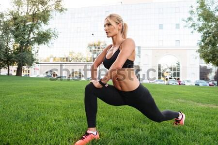 Oldalnézet portré fitnessz nő fülhallgató nyújtás fű Stock fotó © deandrobot