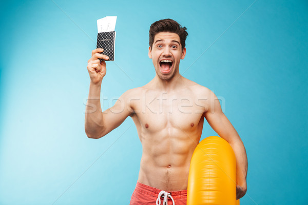 Portrait of a cheerful young shirtless man with inflatable ring Stock photo © deandrobot