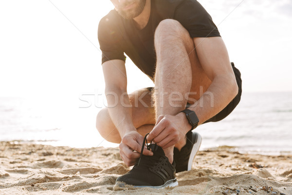 Cropped image of a sportsman tying shoelaces Stock photo © deandrobot