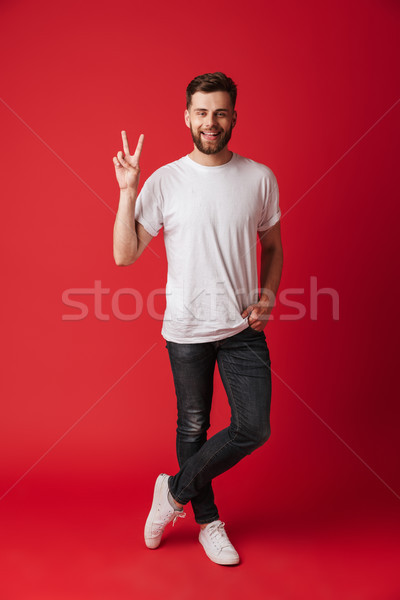 Happy young man standing isolated showing peace gesture. Stock photo © deandrobot
