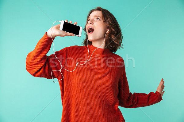 Portrait of a cheerful young woman dressed in sweater Stock photo © deandrobot