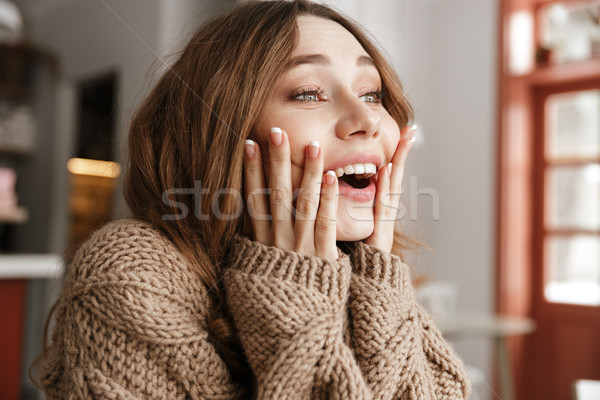 Portrait closeup of astonished woman in knitted sweater, sitting Stock photo © deandrobot