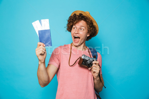 Photo of happy tourist man 18-20 with curly hair wearing backpac Stock photo © deandrobot