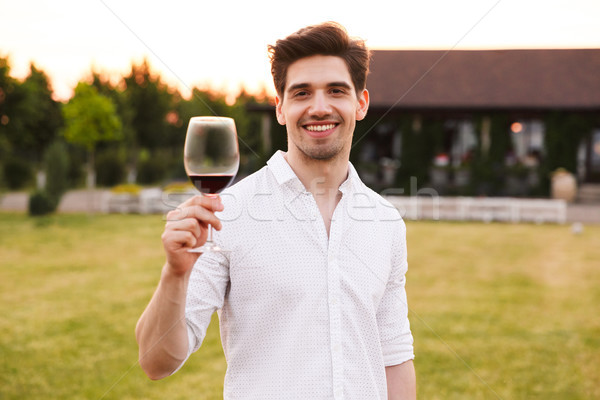 Photo of cheerful young guy wearing white shirt smiling, and hol Stock photo © deandrobot