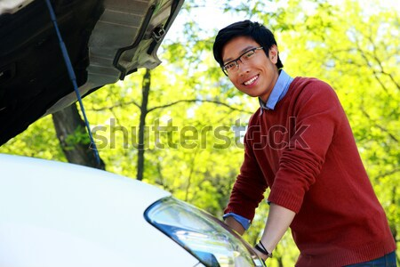 Side view portrait of a young asian man checking his car engine Stock photo © deandrobot