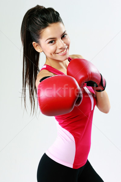 Young smiling woman punching in camera with boxing glove on gray background Stock photo © deandrobot