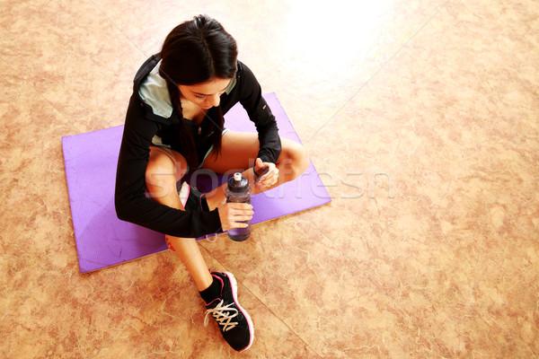 Genç uygun kadın oturma yoga mat Stok fotoğraf © deandrobot