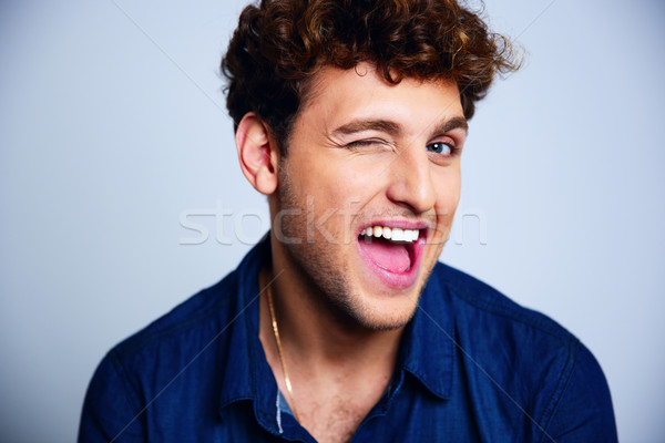 Laughing young man winking over blue background Stock photo © deandrobot