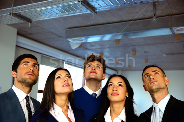 Serious business people looking up with dreaming expression Stock photo © deandrobot