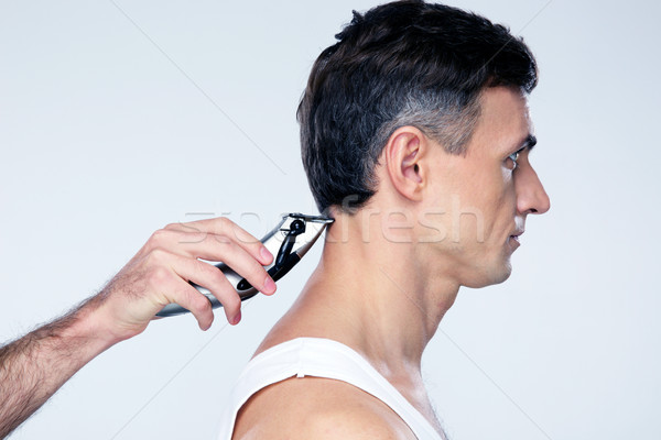 Side view portrait of a man cuts hair with hair clipper on back of the head Stock photo © deandrobot