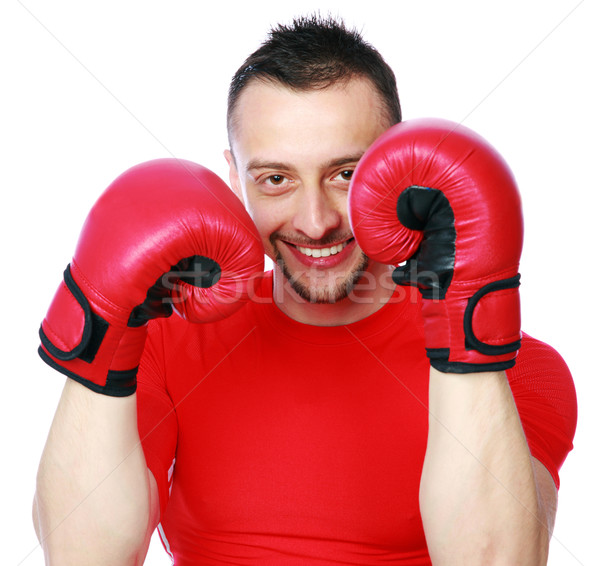 Portrait of a cheerful sportsman in boxing gloves over white background Stock photo © deandrobot