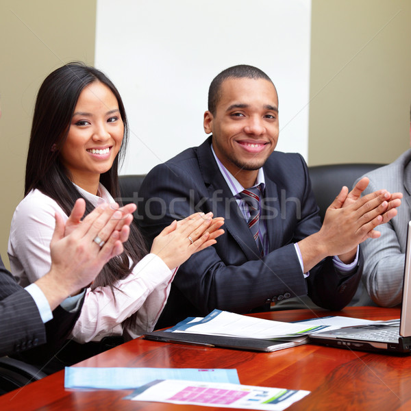 Multi ethnic business group greets you with clapping and smiling. Focus on woman Stock photo © deandrobot