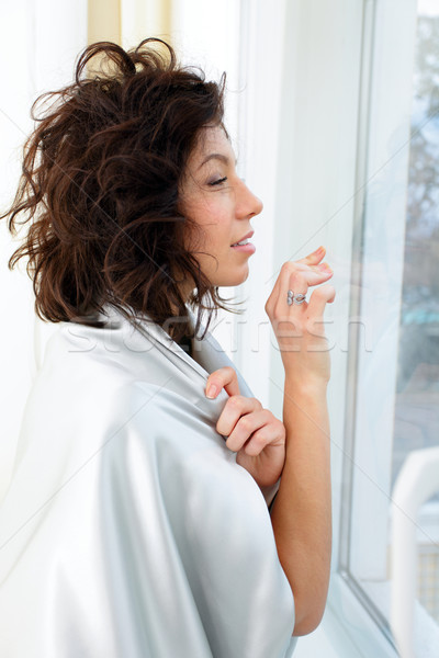 Beautiful woman wrapped in blanket standing at the window and waiting Stock photo © deandrobot