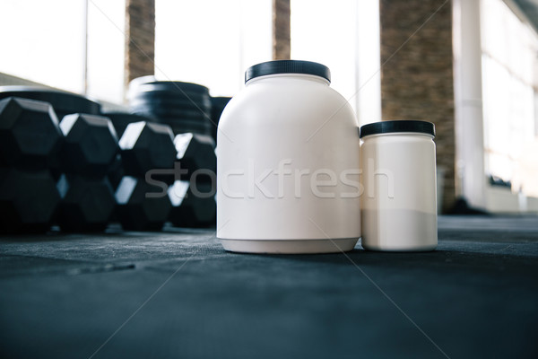 Plastic containers with sports nutrition on dumbbells Stock photo © deandrobot