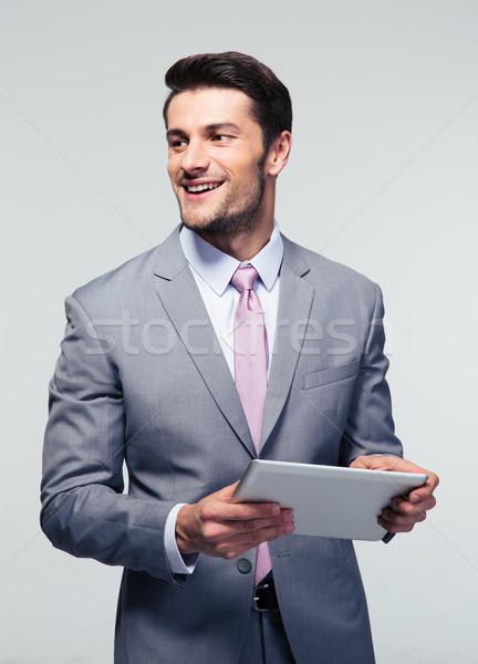 Happy businessman holding tablet computer Stock photo © deandrobot